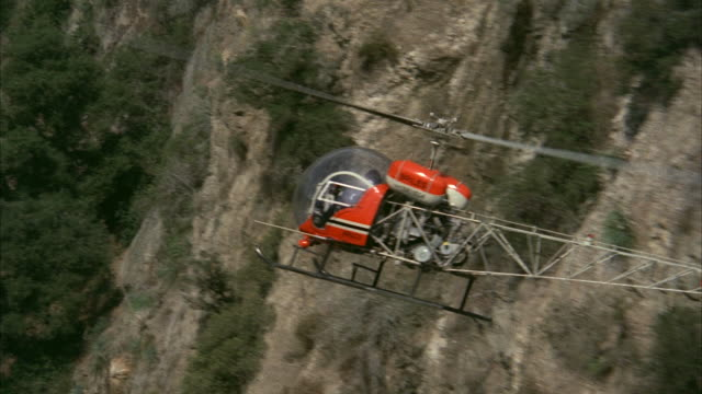 ms ts shot of small bell helicopter (red) flying fast and dangerously close to rugged southern california semiarrid canyon walls - hubschrauber stock-videos und b-roll-filmmaterial