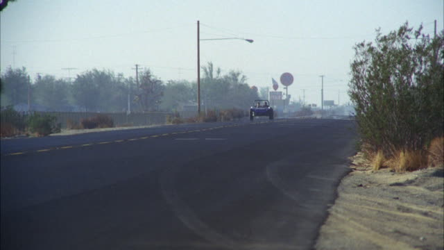 ms pan shot of small blue dune buggy desert on highway  - dune buggy stock videos and b-roll footage