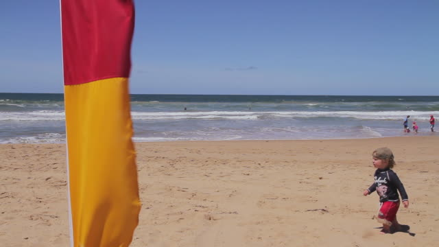 MS Shot of small child passing near lifeguard flags / Melbourne, Victoria, Australia