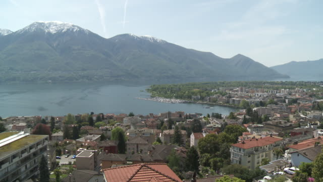 ws shot of small cityscape located surrounded by mountain at lake maggiore / locarno, tessin, switzerland - ticino canton stock videos and b-roll footage