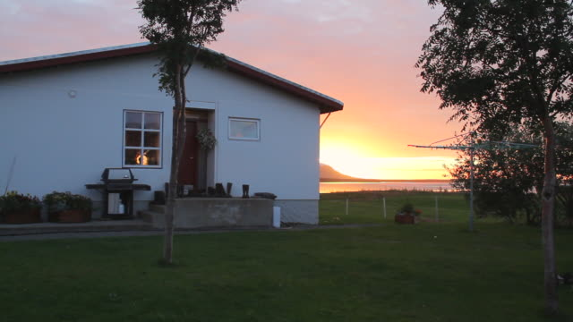 MS Shot of small home sits with sun set behind cliffside on ocean / Skagafjorour, Nordhurland Vestra, Iceland