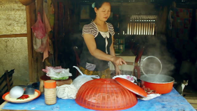 MS SLO MO Shot of small local restaurant with women cooking / Nong Khio, Luang Prabang, Laos