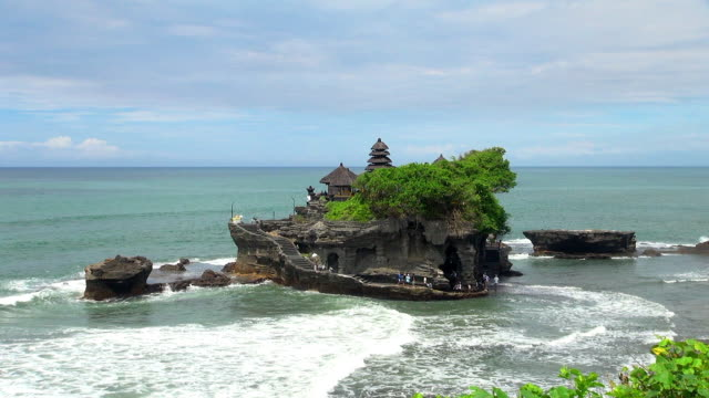 shot of small rock island temple in bali indonesia - gemeinsam gehen stock-videos und b-roll-filmmaterial