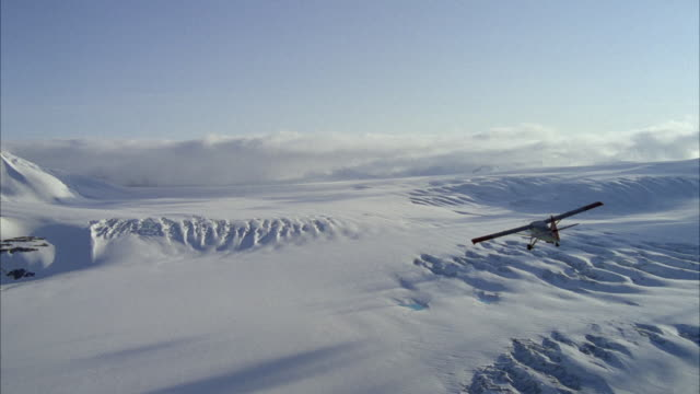 WS AERIAL Shot of small single engine airplane flying over arctic landscape