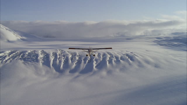 ws aerial shot of small single engine airplane flying over arctic landscape - arctic stock videos & royalty-free footage