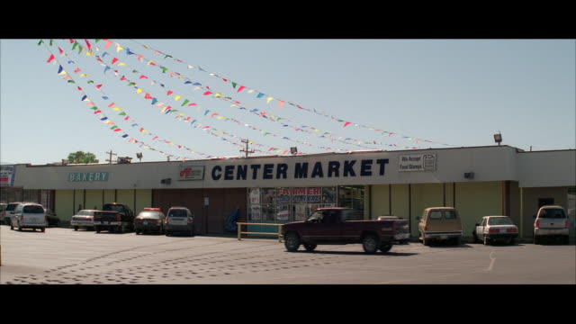 stockvideo's en b-roll-footage met ms shot of small super market and parking lot / unspecified - buitenopname