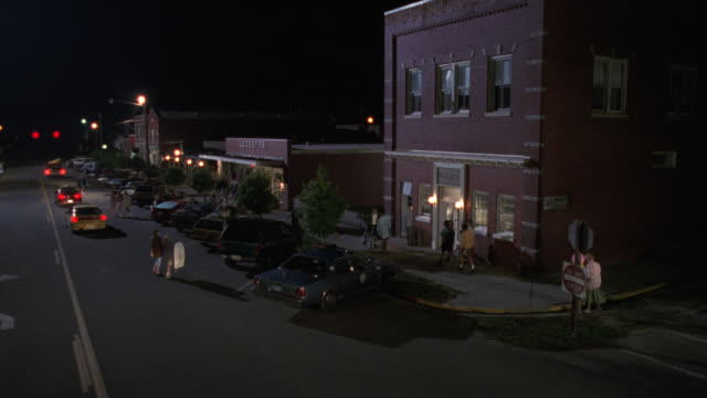 MS Shot of small town red brick two story police station cars and people