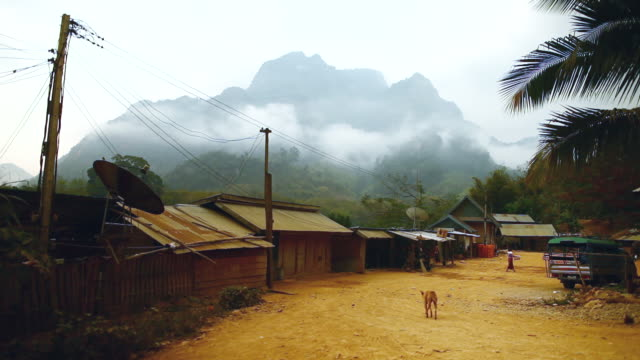 ws shot of small village street in front side with primitive structures dog looking at towards and woman throwing water from bucket with mountain and clouds in back side / village near muang ngoi, luang prabang, laos - small stock videos & royalty-free footage