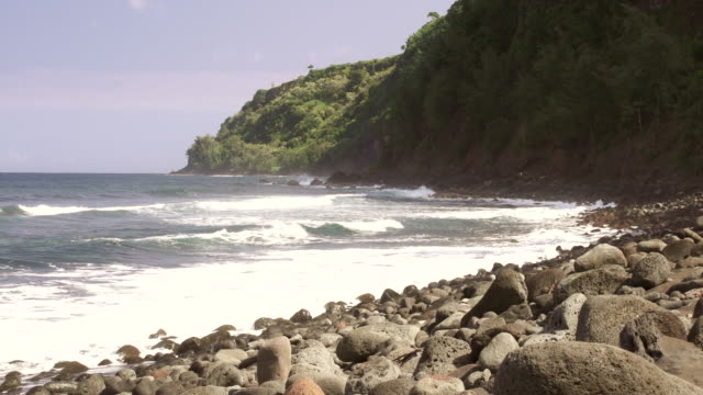 ms shot of small waves crashing into rocky beach and mountains in distant / kauai, hawaii, united states - wiese stock videos & royalty-free footage