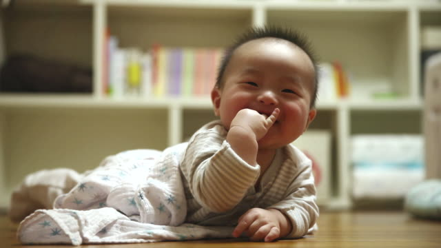 MS Shot of Smiling Korean baby lying on stomach / Jeju, Jeju-do, South Korea