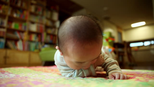 cu shot of smiling korean baby turning over and lying on stomach / jeju, jeju-do, south korea  - 男の赤ちゃん一人点の映像素材/bロール