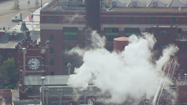 ms aerial shot of smoke billowing around clocktower at anheuser busch brewery / st louis, missouri, united states - anheuser busch brewery missouri stock videos and b-roll footage