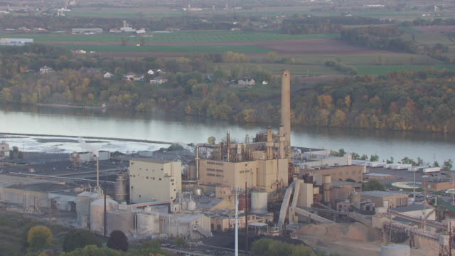 CU AERIAL ZO Shot of smokestacks billowing out steam and pull back to WS Heart of the Valley Metropolitan Sewerage District and Fox River / Appleton, Wisconsin, United States