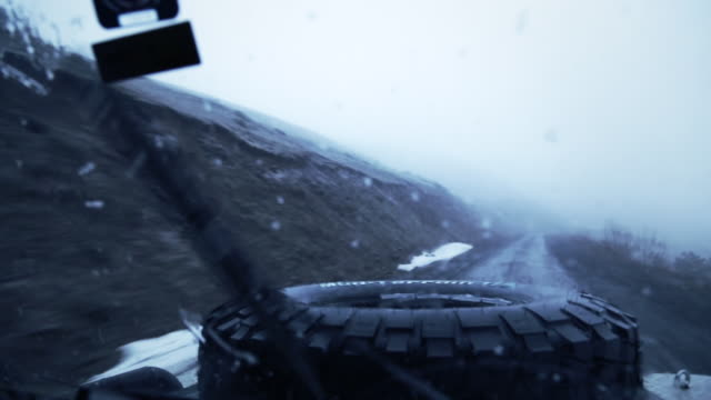 pov shot of snow falling on wind shield of offroad vehicle while driving on a dirt road in eastern anatolia. - anatolia stock videos and b-roll footage
