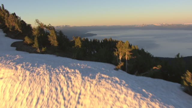 ms aerial shot of snowy peak with pine trees to lake tahoe in morning with mountains and forest in shade / nevada, united states - californian sierra nevada stock videos and b-roll footage