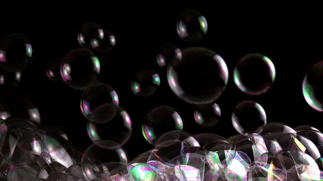 ECU SLO MO Shot of Soap bubbles floating over black background / Calvados, Normandy, France