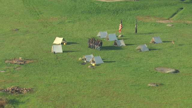 ms aerial ts shot of soldier reenactors standing in uniform by tents gettysburg national military park / pennsylvania, united states - historische nachstellung stock-videos und b-roll-filmmaterial