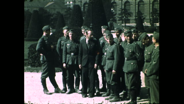 shot of soldier with gun standing guard by the doorway while people passes in the foreground; group of soldiers walking toward camera; group of... - nazism stock videos & royalty-free footage