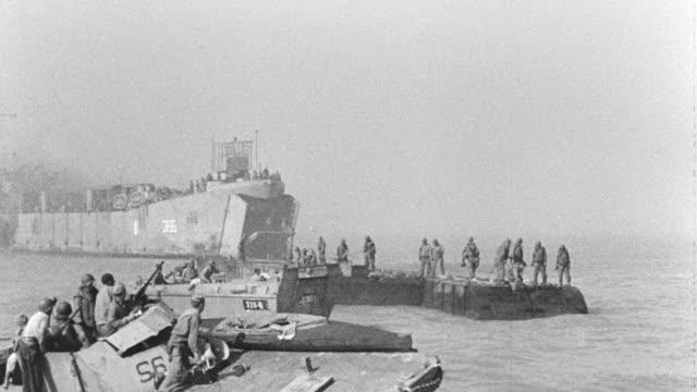 vídeos de stock, filmes e b-roll de ws shot of soldiers build water floating bridge for moving army vehicles and soldiers - navio de desembarque de doca