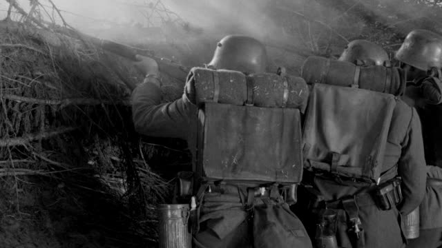 ms shot of soldiers engaged in combat, firing their weapons from behind hedgerow  - traditional helmet stock videos and b-roll footage