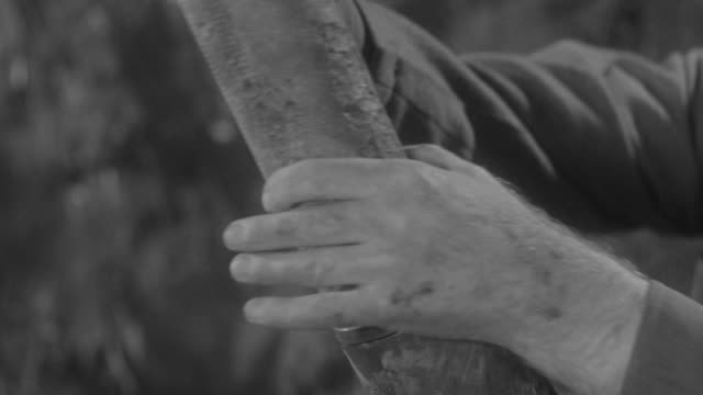 CU Shot of soldiers hand while he's reloading large weapon