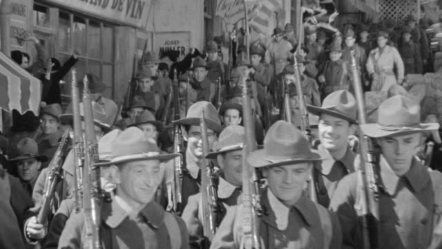 ms shot of soldiers marching near market place - military parade stock videos and b-roll footage
