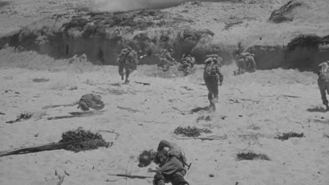 ms shot of soldiers running and taking cover at omaha beach - omaha beach stock videos and b-roll footage