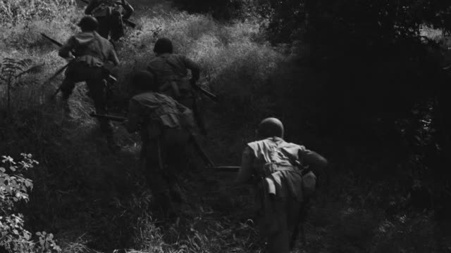 ms shot of soldiers running through brushes in jungle area - traditional helmet stock videos and b-roll footage