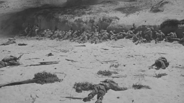 ms pan shot of soldiers taking cover at omaha beach - omaha beach stock videos and b-roll footage