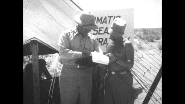 Shot of soldiers under opensided tent in desert wind gauges in foreground / officer standing next to soldier next to tent looking with him at papers...
