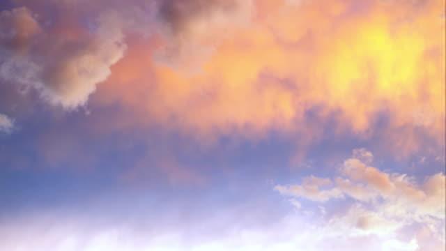 vídeos de stock, filmes e b-roll de shot of some fiery orange clouds with a blue sky. - só céu