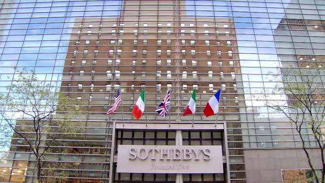 ms la shot of sotheby's headquarters sign with country flags and reflection of building on exterior of building and buses driving by / new york, united states - サザビーズ点の映像素材/bロール
