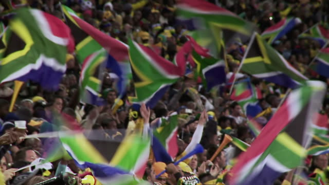 ms pan shot of south african fans blowing vuvuzela's and flying flags / johannesburg, gauteng, south africa - 旗点の映像素材/bロール