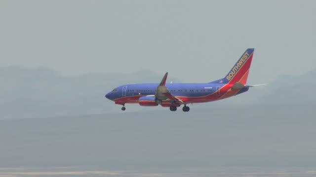 vídeos y material grabado en eventos de stock de ms aerial ts shot of southwest airlines commercial airplane flying into city for landing / las vegas, nevada, united states - southwest usa