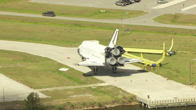 ms aerial shot of space ship sitting on runway with parking lot at kennedy space center / florida, united states - kennedy space center stock-videos und b-roll-filmmaterial