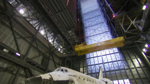 ms td shot of space shuttle discovery inside vehicle assembly building at kennedy space center / cape canaveral, florida, united states - 飛行機格納庫点の映像素材/bロール