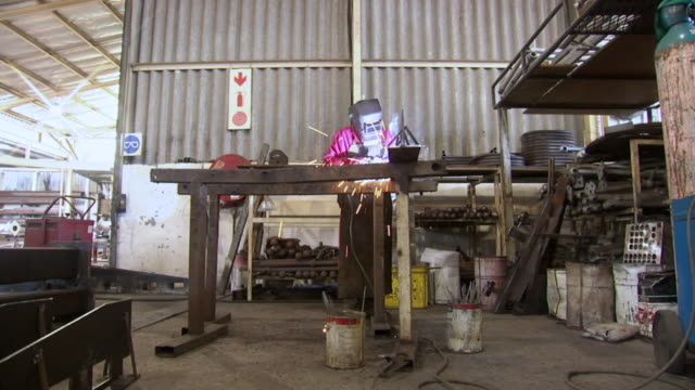 WS Shot of sparks fly as a man welding something together in a factory / Durban, South Africa