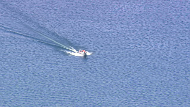 ms aerial shot of speed boat moving in lake at yellowstone national park / wyoming, united states - barca a motore video stock e b–roll