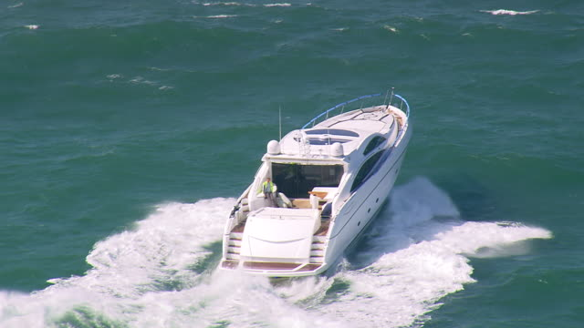 ms aerial ts shot of speed boat running on sea surface / dorset, united kingdom - speed boat stock videos & royalty-free footage