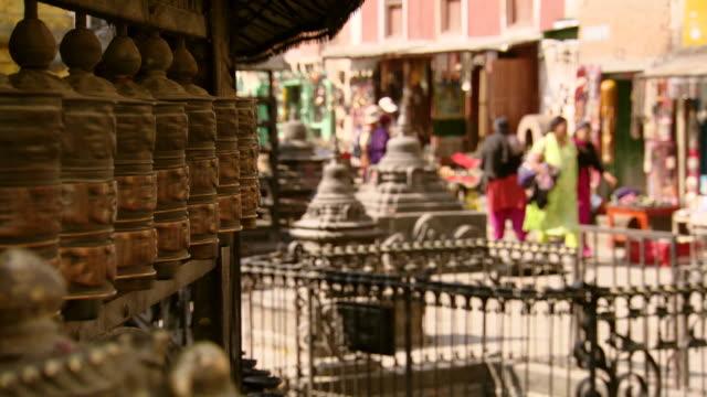 ms pan shot of spinning prayer wheels at boudhanath stupa temple / kathmandu, nepal - kathmandu stock videos & royalty-free footage