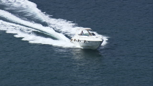 ms aerial shot of spped boat moving in ocean / rio de janeiro, brazil - speed boat stock videos & royalty-free footage