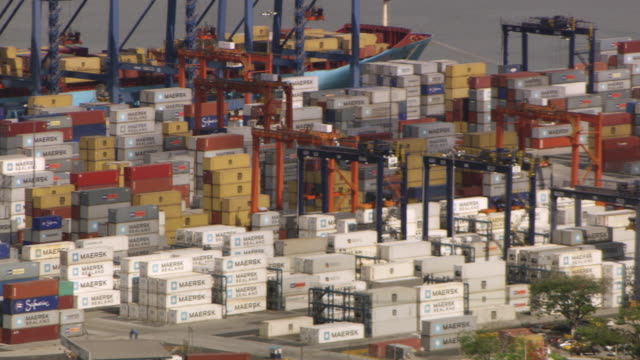 vidéos et rushes de ws pan shot of stacks of shipping containers sit on docks on the panama canal / panama - canal de panama