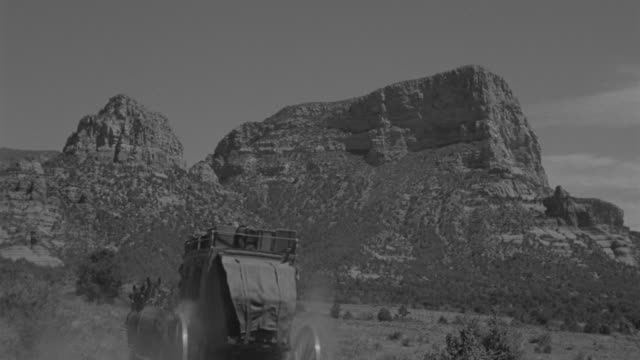 ws shot of stage coach moving through rural desert area with mountain - arbeitstier stock-videos und b-roll-filmmaterial