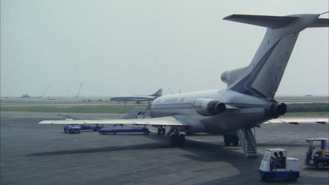 ms pan shot of standing airplane on airport and terminal building - 1978 stock videos and b-roll footage