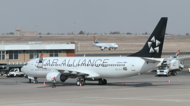 ms shot of star alliance 737-800 being tending while other aircraft taxi in back side / johannesburg, gauteng, south africa - western script stock videos & royalty-free footage