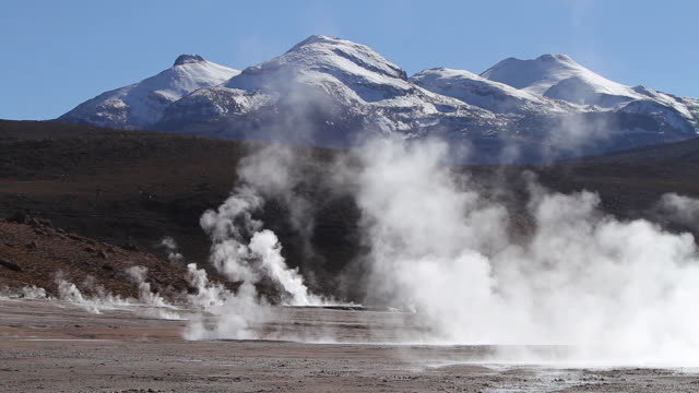 ws shot of static landscape of geyser field with steam coming out from ground with snowy mountains / geiser del tatio, atacama desert, chile - geyser stock videos & royalty-free footage