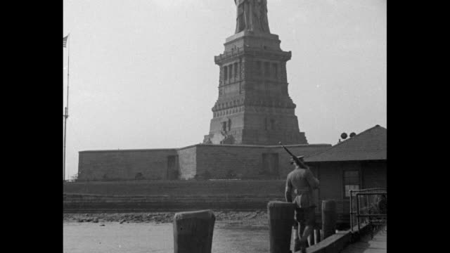 vídeos de stock e filmes b-roll de shot of statue of liberty / closer shot of statue, soldier on guard duty on dock in foreground / shot from below of statue / shot from inside torch... - estatua da liberdade