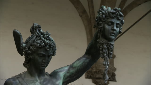 ms ds zo shot of statue of perseus holding head of medusa at piazza della signori / firenze, tuscany, italy - statuetta video stock e b–roll