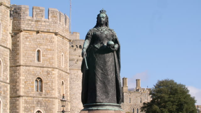 Shot of statue of Queen Victoria standing next to Windsor Castle.