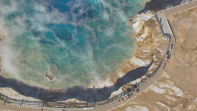 ms aerial ts zo shot of steam rising and people walking near edge to reveal excelsior geyser crater in yellowstone national park / wyoming, united states - イエローストーン国立公園点の映像素材/bロール